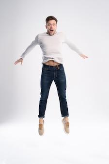 Mann im lässigen t-shirt und in den jeans, die lokal über weißem hintergrund springen.