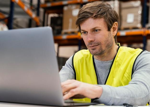 Mann im lager, das am laptop arbeitet