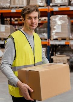 Mann im lager, der mit paketen arbeitet