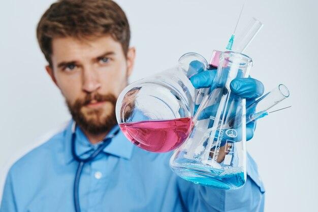 Mann im medizinischen gewand laborassistent mit flüssigkeit im kolben und im hintergrund des chemischen reaktionslichts des stethoskoparztes