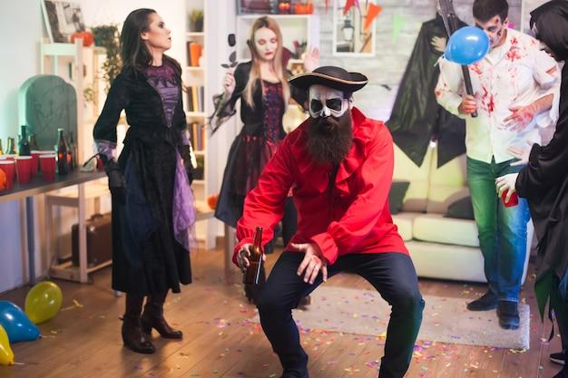 Mann im mittelalterlichen piratenkostüm für halloween. freunde tanzen.