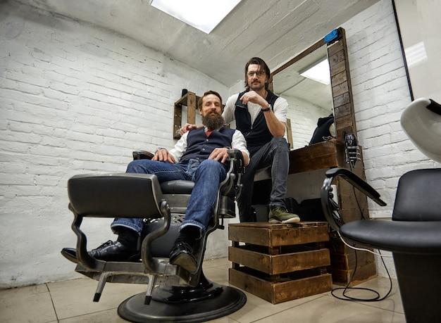 Mann im modernen friseurladen. friseur macht frisur zu einem mann mit langem bart. meisterfriseur frisiert mit schere und kamm