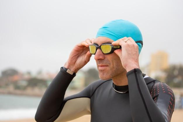 Mann im neoprenanzug mit schutzbrille