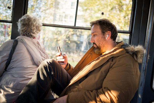 Mann im öffentlichen verkehr, der mit smartphone sitzt, das musik hört