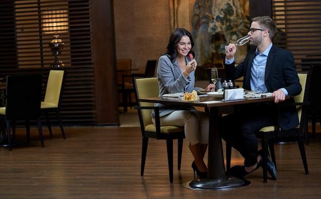 Mann im offiziellen anzug, der ein glas wein anhebt und einen schluck macht, während eine fröhliche dame sushi zum mund bringt