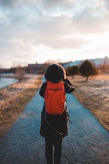 Mann im orange und schwarzen kapuzenpulli, der während des tages auf feldweg steht