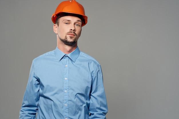 Mann im orangefarbenen helm blaupausen baumeister arbeitsberuf