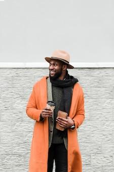 Mann im orangefarbenen mantel, der eine tasse kaffee draußen hält
