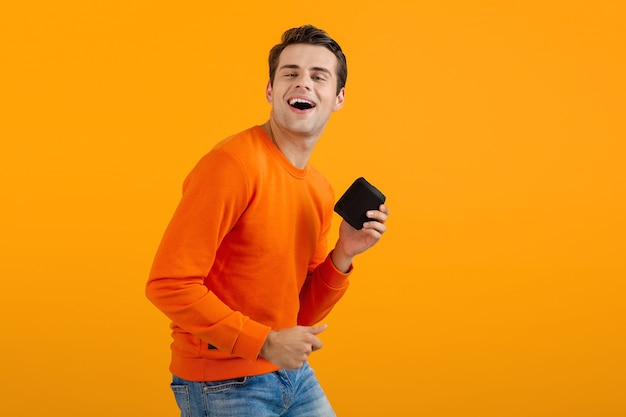 Mann im orangefarbenen pullover, der einen drahtlosen lautsprecher hält, der glücklich musik hört und spaß hat, isoliert auf gelb