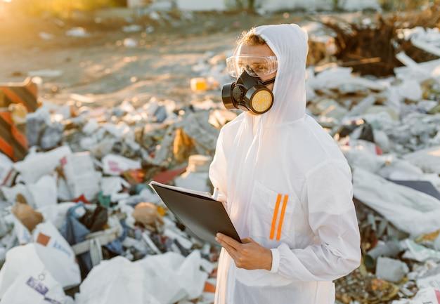 Mann im overall an der müllpille. forschung betreiben. konzept der ökologie, umweltverschmutzung.