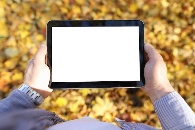 Mann im park hält digitale tablette