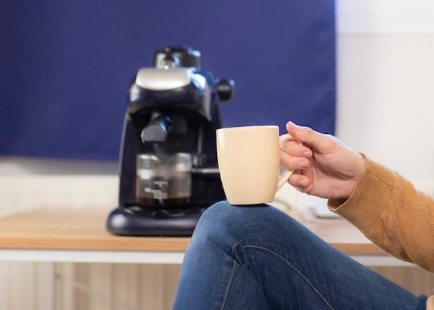 Mann im pullover, der kaffee zu hause trinkt