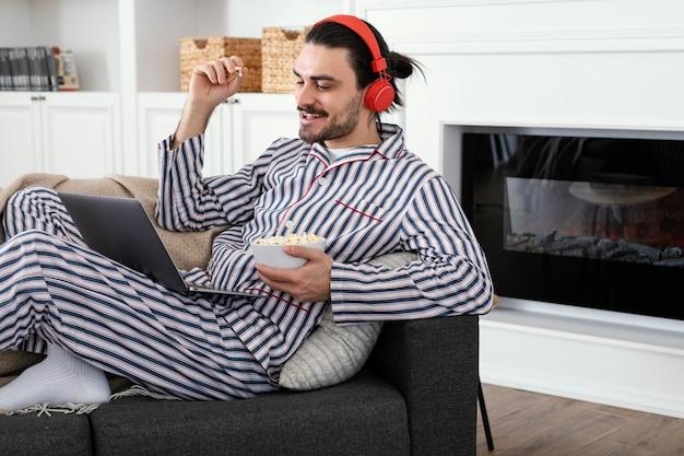 Mann im pyjama, der popcorn isst