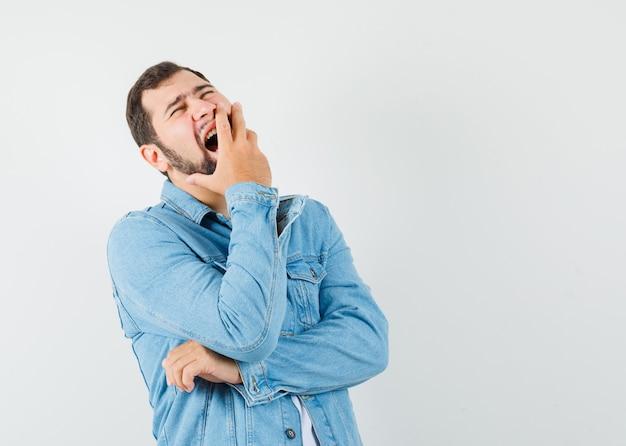 Mann im retro-stil, der mit der hand am mund in jacke, t-shirt gähnt und schläfrig aussieht. vorderansicht.