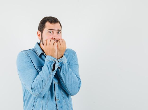 Mann im retro-stil, der seinen mund mit fäusten in jacke, t-shirt bedeckt und verängstigt aussieht. vorderansicht. freier speicherplatz für ihren text