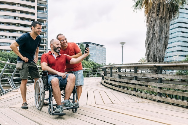 Mann im rollstuhl, der ein foto mit zwei freunden macht