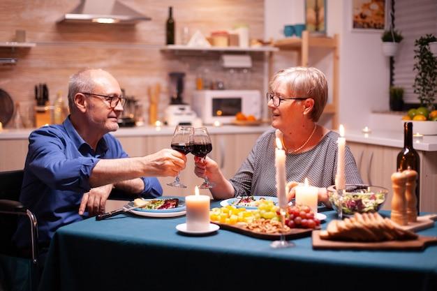 Mann im rollstuhl, essen mit frau und toasten mit gläsern mit rotwein. rollstuhl immobilisierter gelähmter behinderter mann, der zu hause mit seiner frau isst und das essen genießt