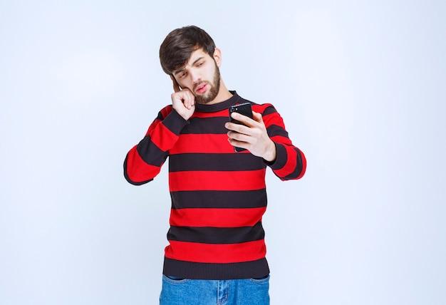 Mann im rot gestreiften hemd, das ein schwarzes smartphone hält und denkt.