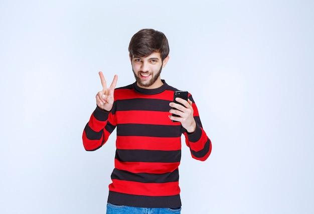 Mann im rot gestreiften hemd, das ein schwarzes smartphone hält und zeigt, dass er neue funktionen genießt.