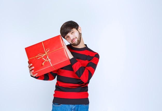 Mann im rot gestreiften hemd, das eine rote geschenkbox hält, sie dem kunden oder seiner freundin liefert und präsentiert. foto in hoher qualität