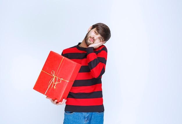 Mann im rot gestreiften hemd, das eine rote geschenkbox hält, sieht müde und schläfrig aus.