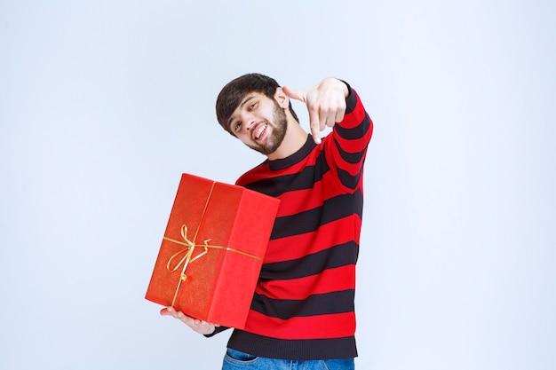 Mann im rot gestreiften hemd, das eine rote geschenkbox hält und die person direkt neben ihm anruft.