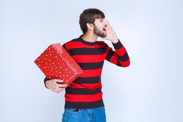 Mann im rot gestreiften hemd, das eine rote geschenkbox hält und jemanden auffordert, es zu liefern.
