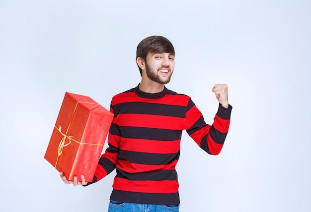 Mann im rot gestreiften hemd, das eine rote geschenkbox hält und sich kraftvoll und positiv fühlt.