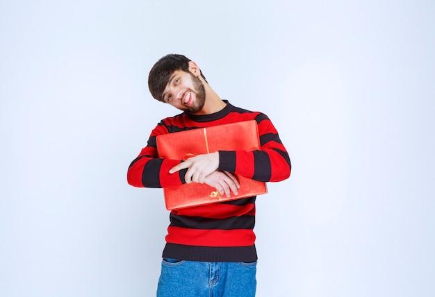 Mann im rot gestreiften hemd, das eine rote geschenkbox hält und sie fest umarmt und mit niemandem teilen möchte.