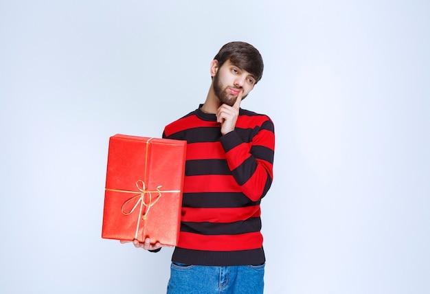 Mann im rot gestreiften hemd, das eine rote geschenkbox hält und verwirrt und nachdenklich aussieht. Kostenlose Fotos