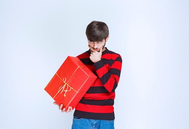 Mann im rot gestreiften hemd, das eine rote geschenkbox hält und verwirrt und nachdenklich aussieht.