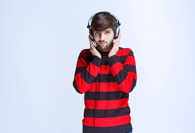 Mann im rot gestreiften hemd, das kopfhörer hört und musik aus seiner playlist auf dem smartphone einstellt.