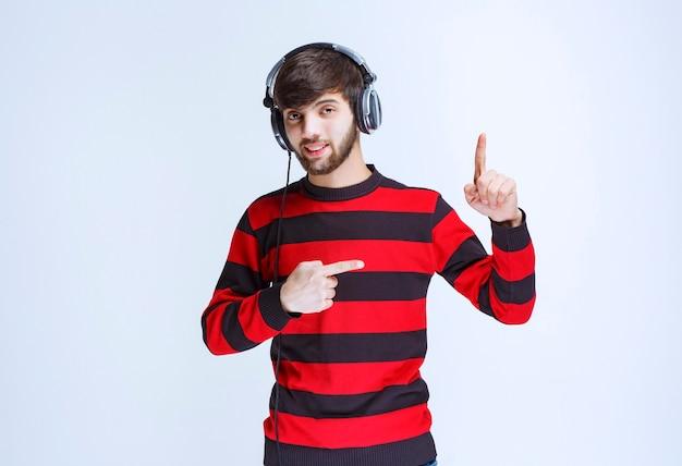 Mann im rot gestreiften hemd, das kopfhörer hört und tanzt oder nach oben zeigt.