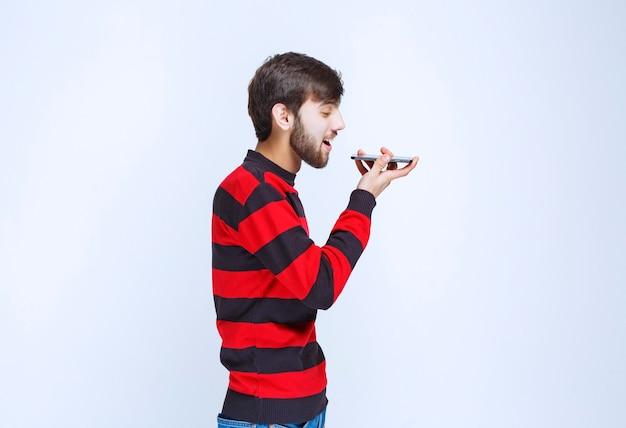 Mann im rot gestreiften hemd, das telefon an den mund hält und eine sprachnachricht sendet.