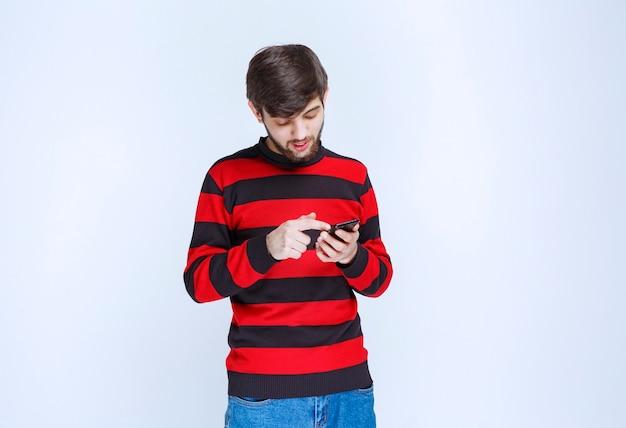 Mann im rot gestreiften hemd, der an seinem smartphone chattet oder sms schreibt.