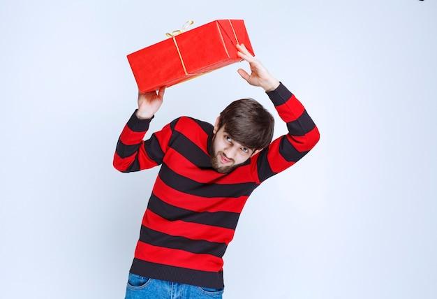 Mann im rot gestreiften hemd hält eine rote geschenkbox, liefert und präsentiert sie