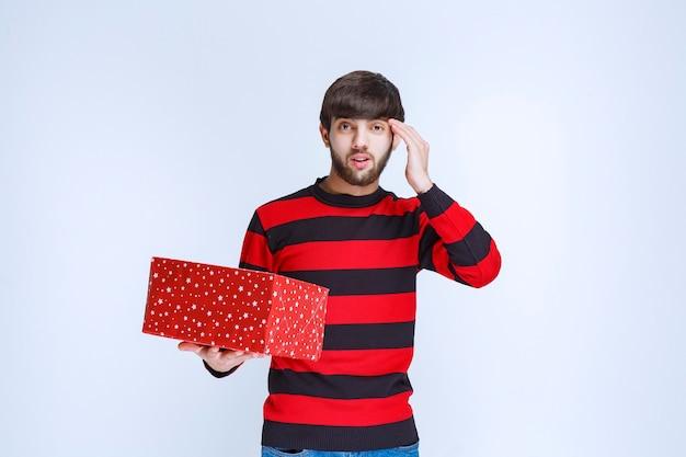 Mann im rot gestreiften hemd mit roter geschenkbox sieht verwirrt und nachdenklich aus.