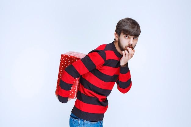 Mann im rot gestreiften hemd versteckt eine rote geschenkbox hinter sich.