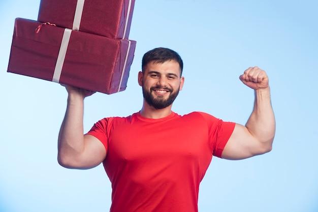 Mann im roten hemd, das eine große geschenkbox hält und stark aussieht.