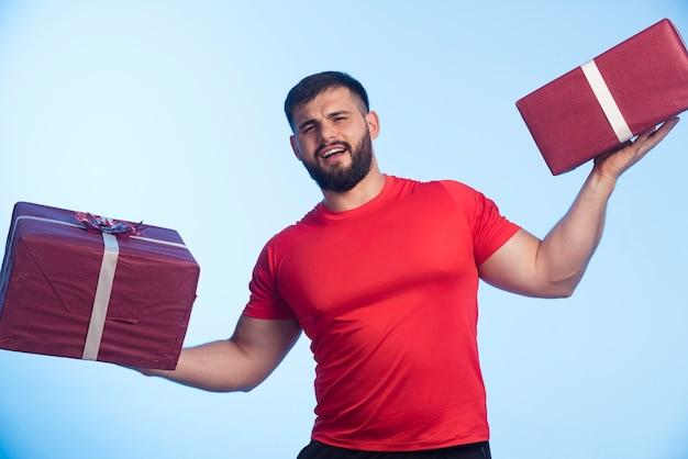 Mann im roten hemd, das geschenkboxen in beiden händen hält.