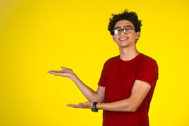 Mann im roten hemd, das präsentation mit handgesten mit freude tut und spaß hat.