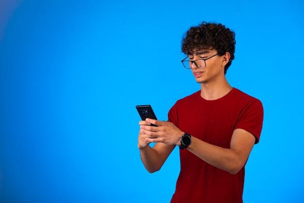Mann im roten hemd, das selfie auf einem smartphone auf blau nimmt