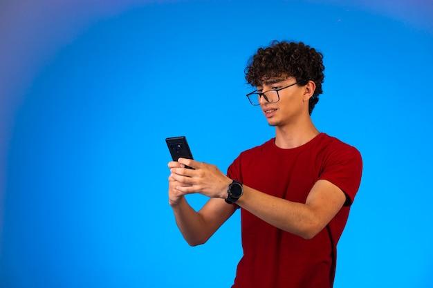 Mann im roten hemd, das selfie auf einem smartphone auf blauem hintergrund nimmt.