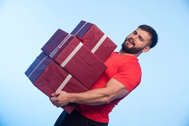 Mann im roten hemd, der einen schweren vorrat an geschenkboxen hält