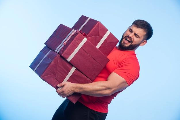 Mann im roten hemd, der einen schweren vorrat an geschenkboxen hält.