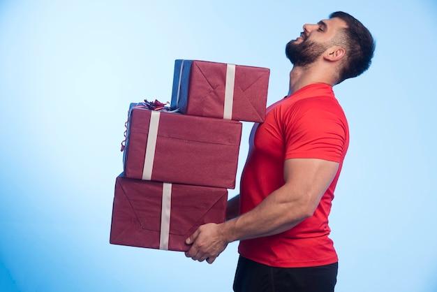 Mann im roten hemd hält einen vorrat an geschenkboxen