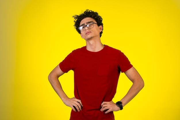 Mann im roten hemd legte seine hände auf seine taille.