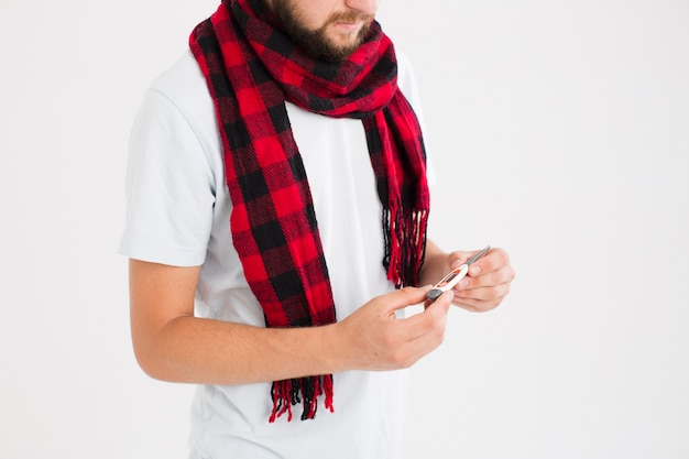Mann im roten karierten schal, der thermometer betrachtet