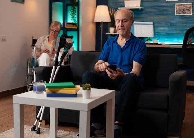 Mann im ruhestand mit smartphone, der zu hause auf der couch sitzt