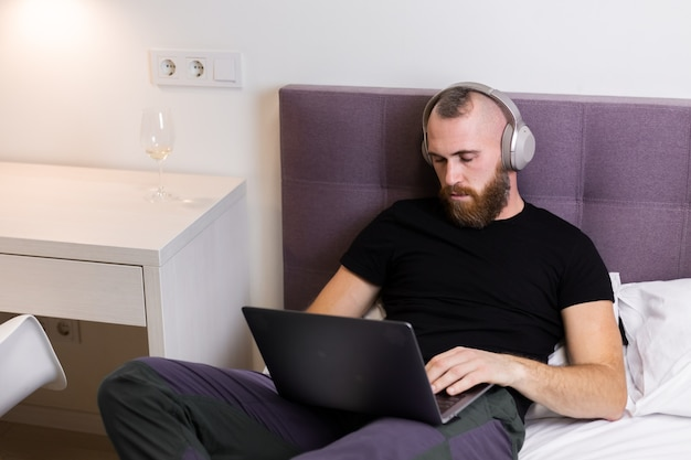 Mann im schlafzimmer auf dem bett schlief vor dem laptop ein